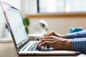 Mann schreibt auf Laptop