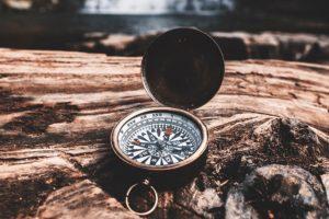 aufgeklappter Kompass auf einem umgestürzten Baumstamm, dahinter ein Wasserfall mit Teich